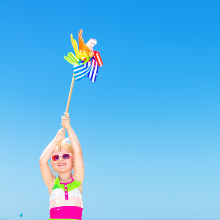 Blue sea, white sand paradise. Full length portrait of happy modern girl in colorful swimsuit on the seashore holding colorful windmill toy Banco de Imagens