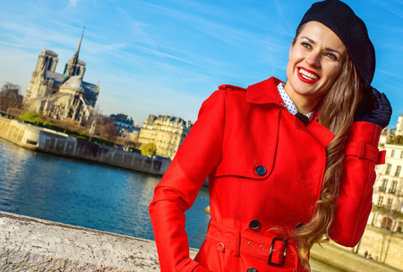 smiling stylish traveller woman in red trench coat on embankment in Paris, France looking into the distance