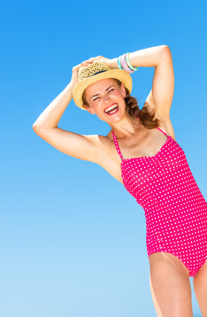 happy modern woman in colorful red swimsuit on the seacoast