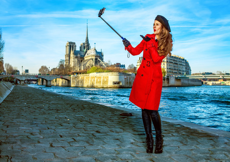 happy young traveller woman in red trench coat on embankment near Notre Dame de Paris in Paris, France taking selfie using selfie stick