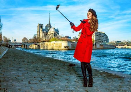 Feliz mujer joven viajero en gabardina roja en terraplén cerca de Notre Dame de Paris en París, Francia tomando selfie usando selfie stick