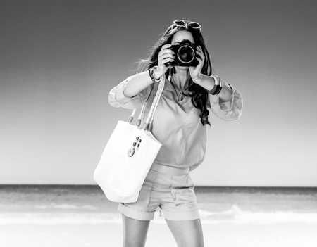 Perfect summer. woman in shorts and yellow blouse with white beach bag on the beach with digital camera taking photo Stock Photo
