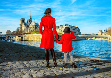 Bright in Paris. Seen from behind modern mother and child travellers in red coats standing on embankment near Notre Dame de Paris in Paris, France