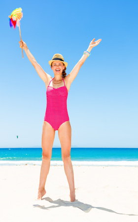 Blue sea, white sand paradise. Full length portrait of happy modern woman in bright red swimsuit on the seashore with colorful windmill toy rejoicing