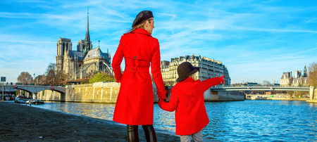 Seen from behind stylish mother and daughter travellers in red coats on embankment near Notre Dame de Paris in Paris, France pointing at something