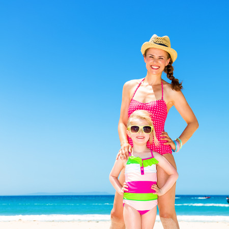 Full length portrait of happy modern mother and daughter in colorful swimsuit standing on the seashore