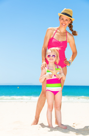 Full length portrait of happy young mother and daughter in bright beachwear on the beach holding starfish