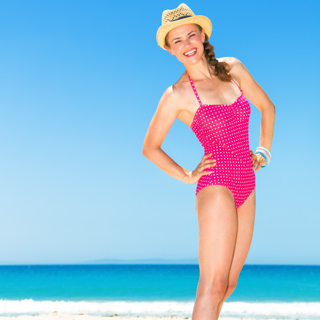 Full length portrait of smiling young woman in colorful red swimwear standing on the beach