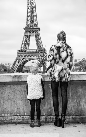 Seen from behind smiling modern mother and child with Christmas tree against Eiffel tower in Paris, France sightseeing