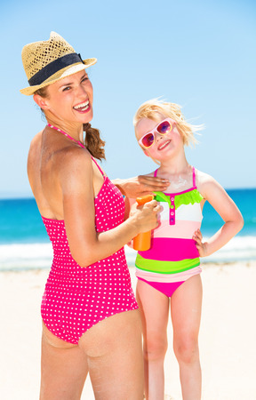 smiling young mother and daughter in colorful swimwear on the beach applying suntan lotion