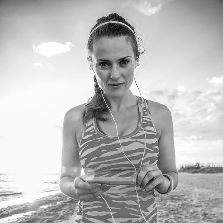 active healthy woman in sports gear on the beach with headphones listening to the music