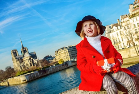 Bright in Paris. happy trendy girl in red coat on embankment near Notre Dame de Paris in Paris, France with Christmas present box looking into the distance 版權商用圖片