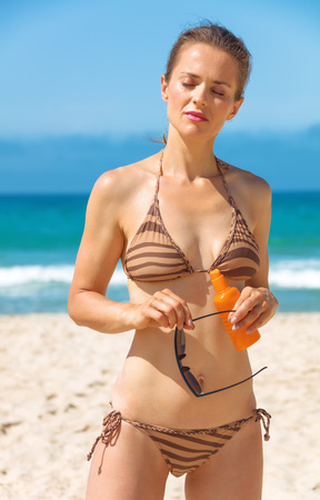 Blue sea, white sand paradise. modern woman in swimwear on the beach with sun block and sunglasses