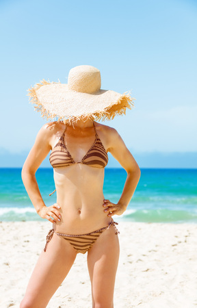 Blue sea, white sand paradise. young woman in bikini on the seacoast hiding behind beach straw hat