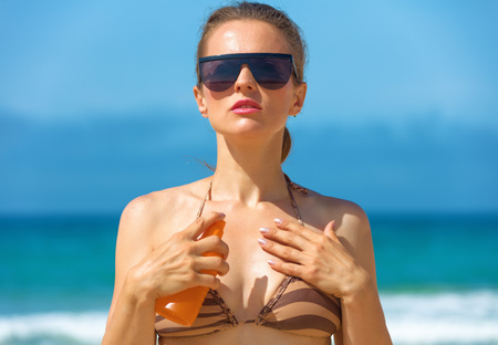 Blue sea, white sand paradise. Portrait of modern woman in sunglasses and swimsuit on the seashore applying SPF