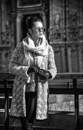Rediscovering things everybody love in Milan. elegant woman in fur coat and sunglasses in Milan, Italy looking into the distance while holding digital photo camera Stock fotó