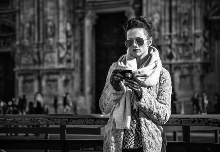 Rediscovering things everybody love in Milan. trendy traveller woman in fur coat and sunglasses in the front of Cathedral in Milan, Italy viewing photos on camera Stock fotó