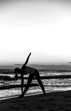 Refreshing wild sea side workout. Silhouette. Full length portrait of young woman in sports gear on the beach workout