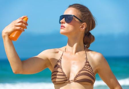 Blue sea, white sand paradise. Portrait of young woman in sunglasses and beachwear on the seashore applying sun cream