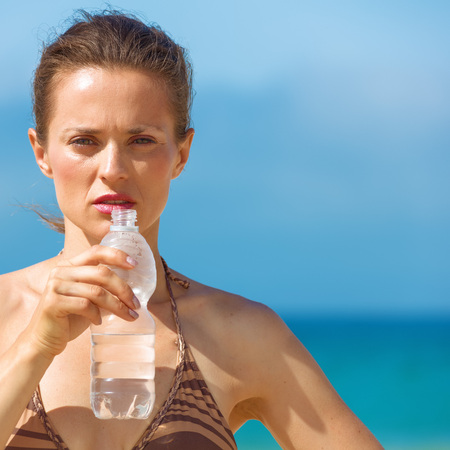 Blue sea, white sand paradise. modern woman in bikini on the beach drinking water from bottle