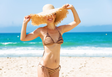 Blue sea, white sand paradise. young woman in bikini and beach straw hat on the seacoast