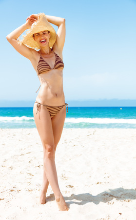 Blue sea, white sand paradise. Full length portrait of smiling young woman in swimwear and beach straw hat on the seashore
