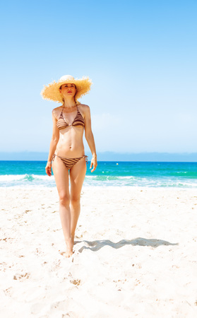 Blue sea, white sand paradise. Full length portrait of modern woman in bikini and beach straw hat on the seashore walking
