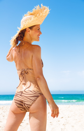 Blue sea, white sand paradise. smiling modern woman in swimsuit and beach straw hat on the seacoast looking aside