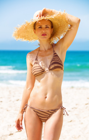 Blue sea, white sand paradise. Portrait of modern woman in beachwear and straw hat on the seashore