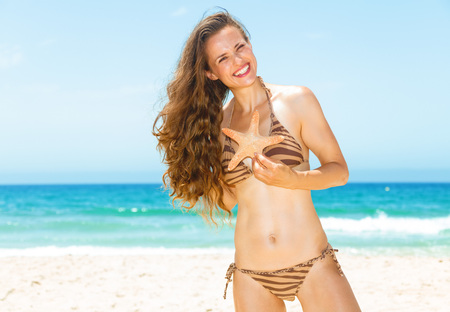 Blue sea, white sand paradise. happy young woman with long brunette hair in swimsuit on the seashore holding starfish Stock Photo