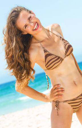 Blue sea, white sand paradise. smiling modern woman with long brunette hair in swimwear on the beach