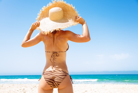 Blue sea, white sand paradise. Seen from behind young woman in swimsuit and beach straw hat on the seashore looking into the distance