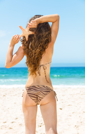 Blue sea, white sand paradise. Seen from behind modern woman with long brunette hair in beachwear on the seashore holding starfish Stock Photo