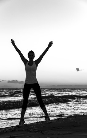 Refreshing wild sea side workout. Silhouette. Full length portrait of fit woman in sports gear on the beach rejoicing Stock Photo