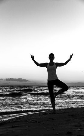 Refreshing wild sea side workout. Silhouette. Full length portrait of healthy woman in sportswear on the seashore doing yoga