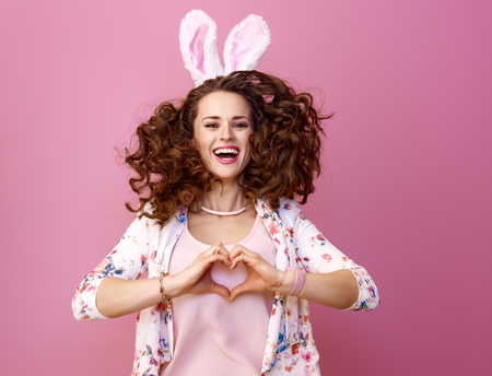 Festive bunny and eggs season. cheerful young woman in Easter bunny ears isolated on pink background jumping  and showing heart shaped hands Stock Photo