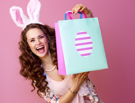 Festive bunny and eggs season. happy stylish woman in Easter bunny ears on pink background showing Easter shopping bag