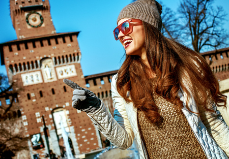 Rediscovering things everybody love in Milan. happy trendy tourist woman near Sforza Castle in Milan, Italy pointing on something Banque d'images - 96653046