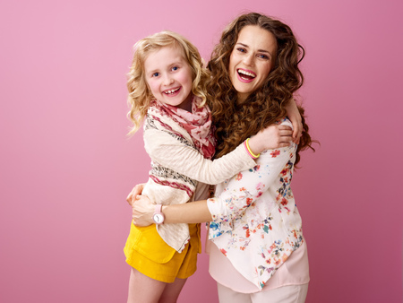 Pink Mood. Portrait of smiling stylish mother and daughter with wavy hair isolated on pink background embracing Banco de Imagens