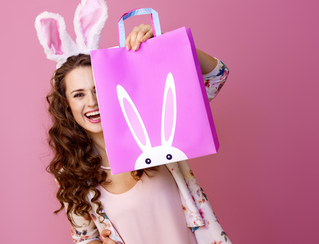 Festive bunny and eggs season. happy modern woman in Easter bunny ears isolated on pink hiding behind Easter shopping bag Stock Photo