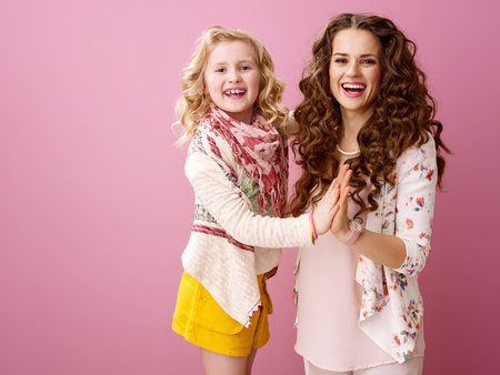 Pink Mood. smiling modern mother and child with wavy hair on pink background clapping hands