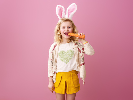 Festive bunny and eggs season. smiling modern girl in Easter bunny ears isolated on pink eating carrot