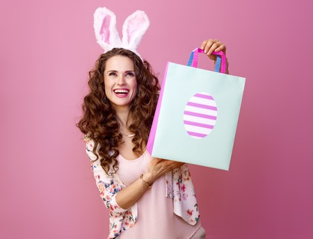 Festive bunny and eggs season. happy modern woman in Easter bunny ears isolated on pink background with Easter shopping bag looking at copy space