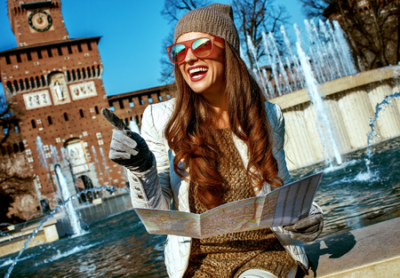 Rediscovering things everybody love in Milan. smiling modern traveller woman near Sforza Castle in Milan, Italy holding map and pointing Banque d'images - 99977086