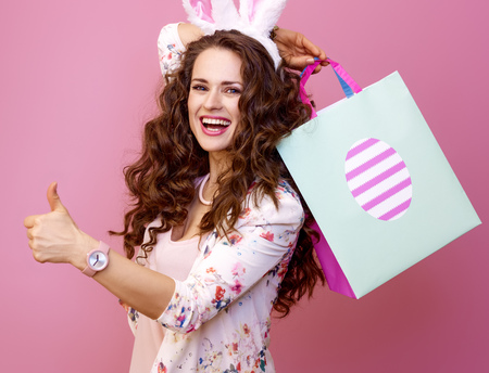 Festive bunny and eggs season. happy modern woman in Easter bunny ears isolated on pink background with Easter shopping bag showing thumbs up Stock Photo