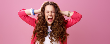 Pink Mood. happy young woman with long wavy brunette hair on pink background