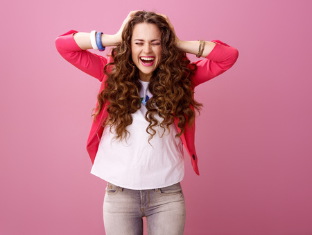 Pink Mood. Portrait of cheerful stylish woman with long wavy brunette hair isolated on pink Фото со стока