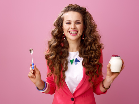 Pink Mood. Portrait of happy trendy woman with long wavy brunette hair isolated on pink background with farm organic yogurt and spoon