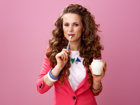 Pink Mood. happy modern woman with long wavy brunette hair isolated on pink with farm organic yogurt licking spoon