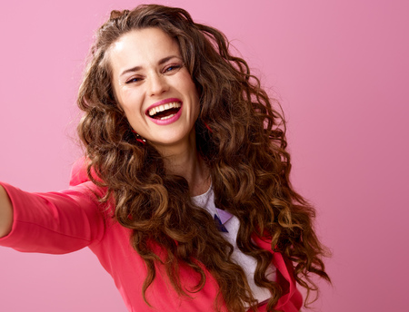Pink Mood. smiling trendy woman with long wavy brunette hair isolated on pink taking selfie